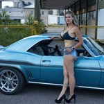 Women Chevrolet Camaro, a woman standing in front of a blue car